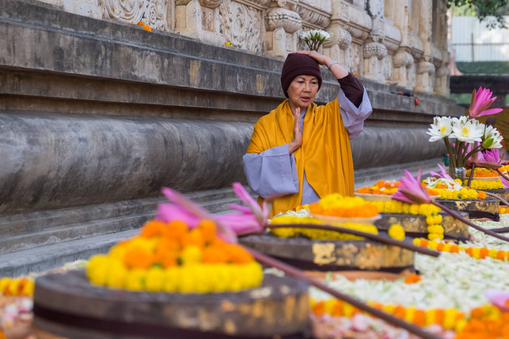 A monk prays offers prayers to the lotus carvings which represent the footsteps of the Buddha