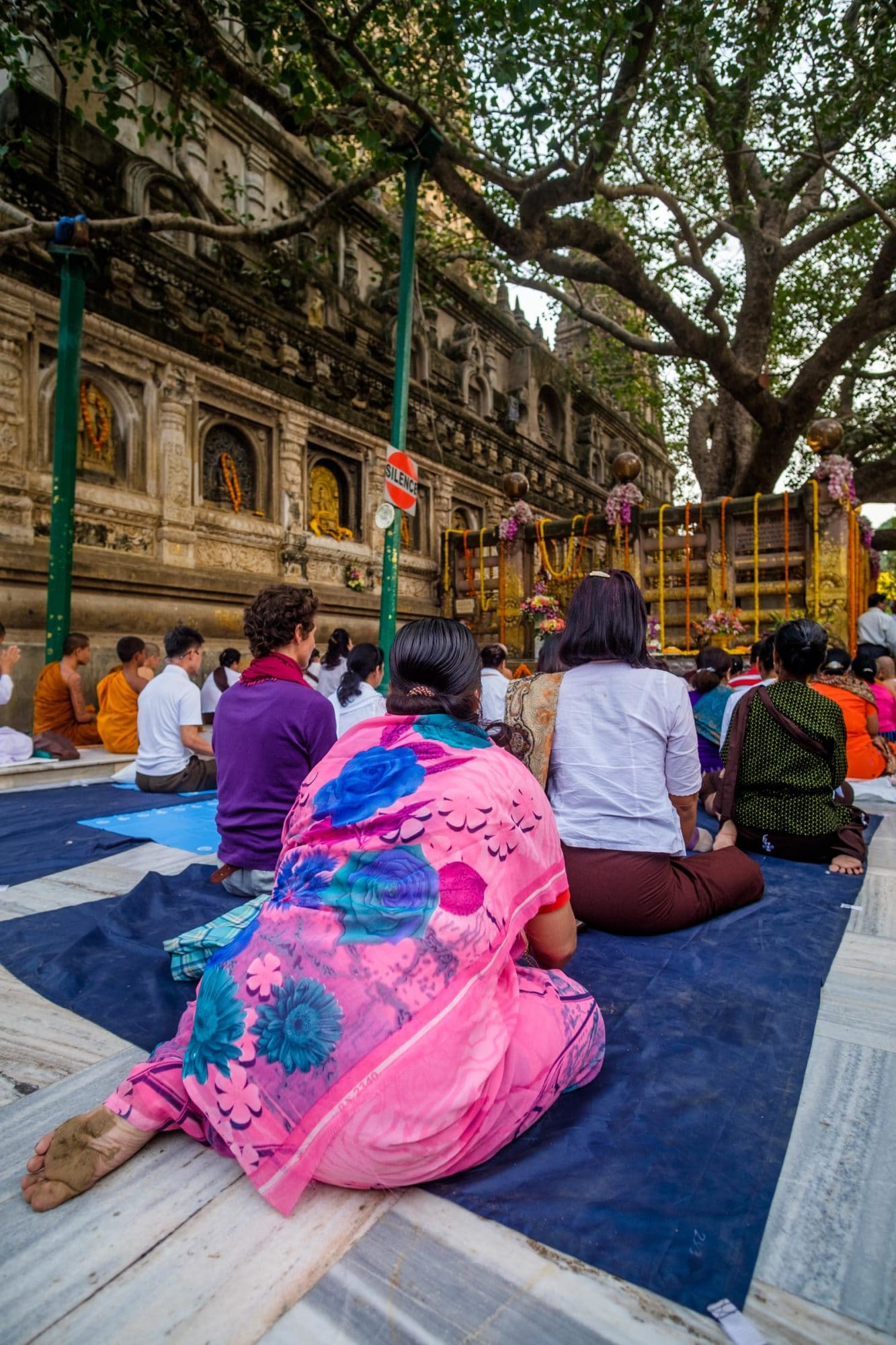 Pilgrims meditate before the Bodhi Tree in Bodhgaya